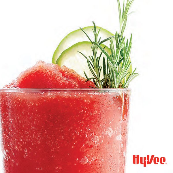 Red cherry limeade slushy in glass with rosemary sprigs and sliced limes