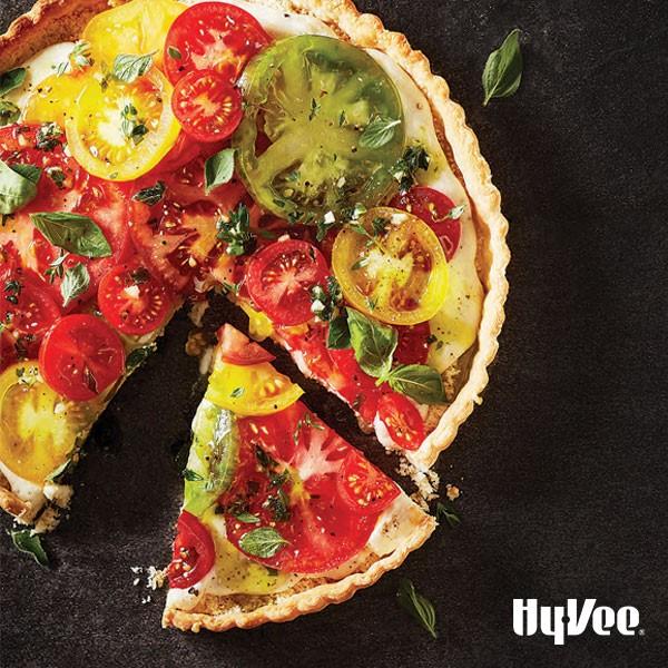 Tart topped with assorted colored tomatoes and topped with fresh herbs