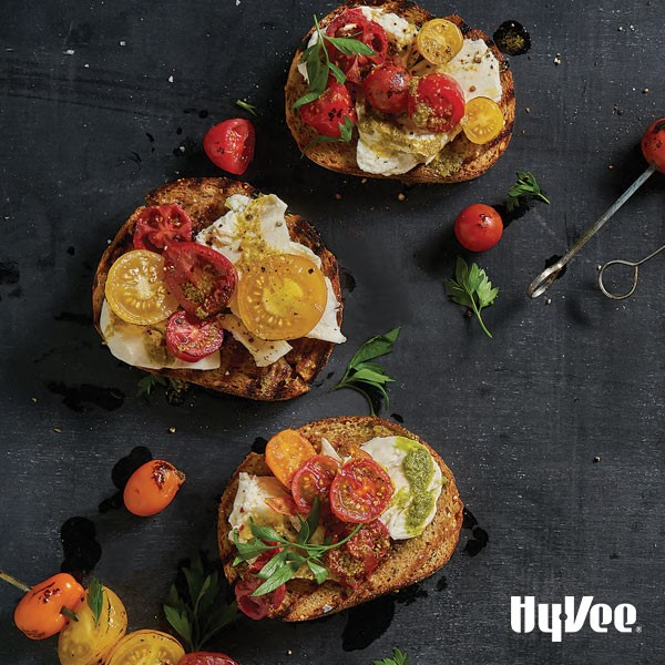 Grilled bread topped with fresh mozzarella, multicolored tomatoes and fresh Italian parsley