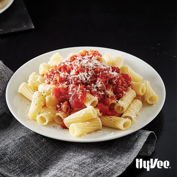 Pasta topped with red sauce and freshly shredded cheese