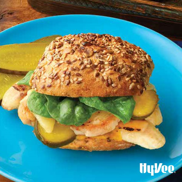 Blue plate with bun topped with pickles, spinach, grilled bananas, and meat on a seeded bun