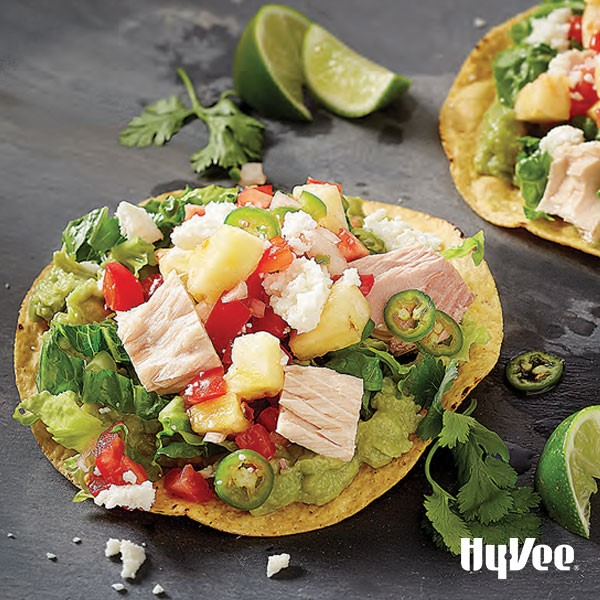 Yellow corn tostadas topped with serrano peppers, tuna, pico de gallo, pineapple, and shredded lettuce