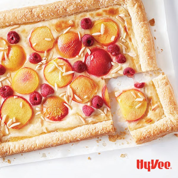 Slab pie with sliced peaches, whole raspberries, and slivered almonds on parchment paper
