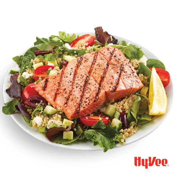 Grilled salmon atop mixed greens, diced cucumbers, halved cherry tomatoes, cooked quinoa, and garnished with fresh lemon wedge