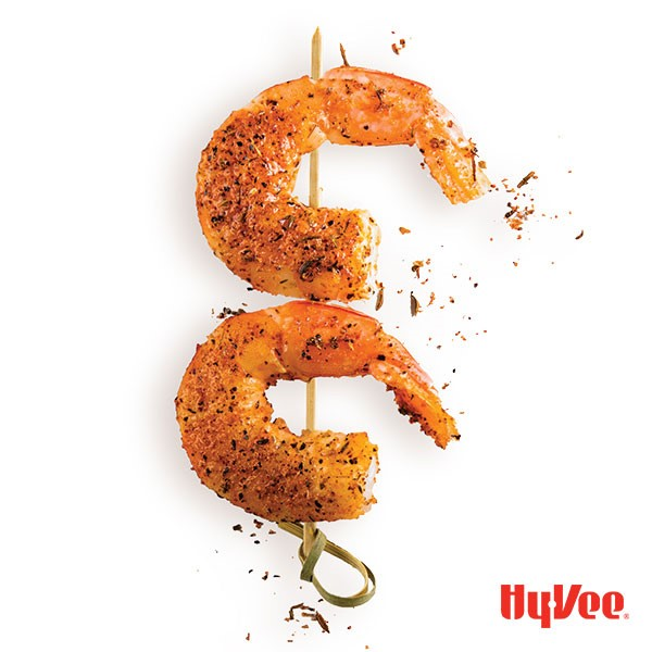 Two tail on shrimp on a wooden skewer sprinkled in seasoning