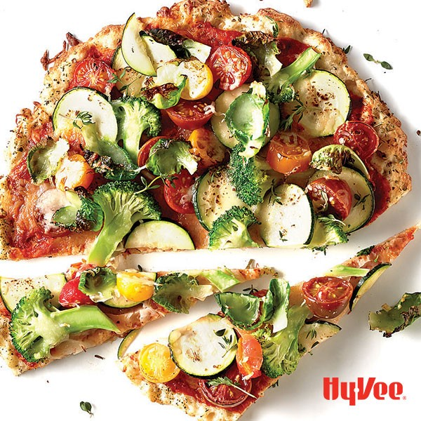 Wedged gluten-free pizza topped with halved red and yellow cherry tomatoes, sliced zucchini, brussel sprouts, and broccoli florets