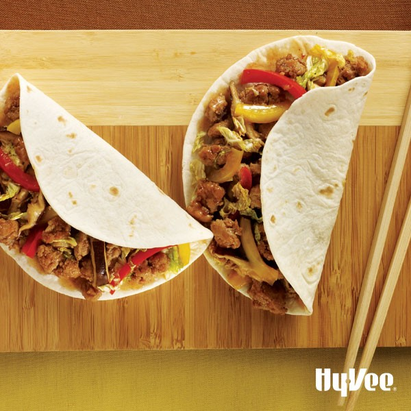 Flour tortillas wrapped around sauteed vegetables and ground cooked pork on a wooden cutting board with wooden chopsticks