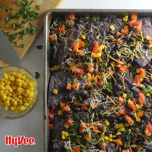 Blue tortilla chips topped with yellow corn, shredded cheese, chopped cilantro, black beans and chopped tomatoes