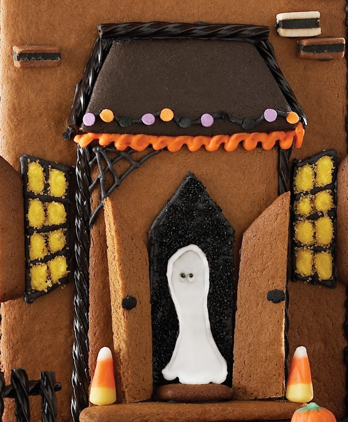 Front of Gingerbread Halloween House Decorated with Frosting and a White Ghost in Front Door