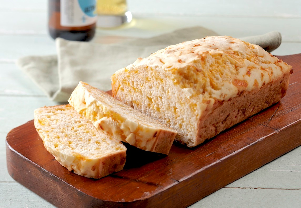 Gluten-Free Cheddar Garlic Beer Bread Sliced on Wooden Cutting Board
