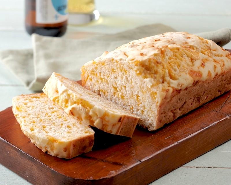 Gluten-Free Cheddar Garlic Beer Bread Sliced on Wooden Cutting Board