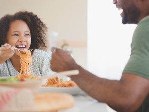 Girl Eating Pasta with Dad in the Kitchen