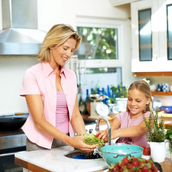 Mother and Daughter Washing Lettuce in Kitchen