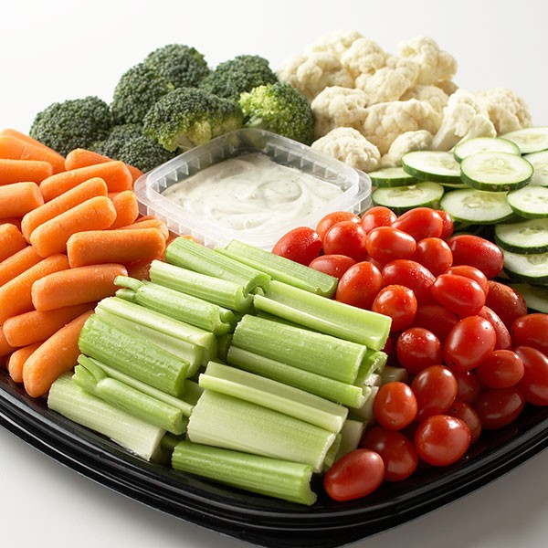vegetable platter with celery, carrots, cherry tomatoes, cucumbers, broccoli, cauliflower, and dip