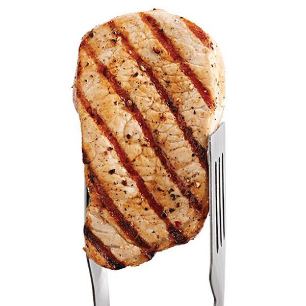 Grilled Pork Chop Held Up by Metal Tongs
