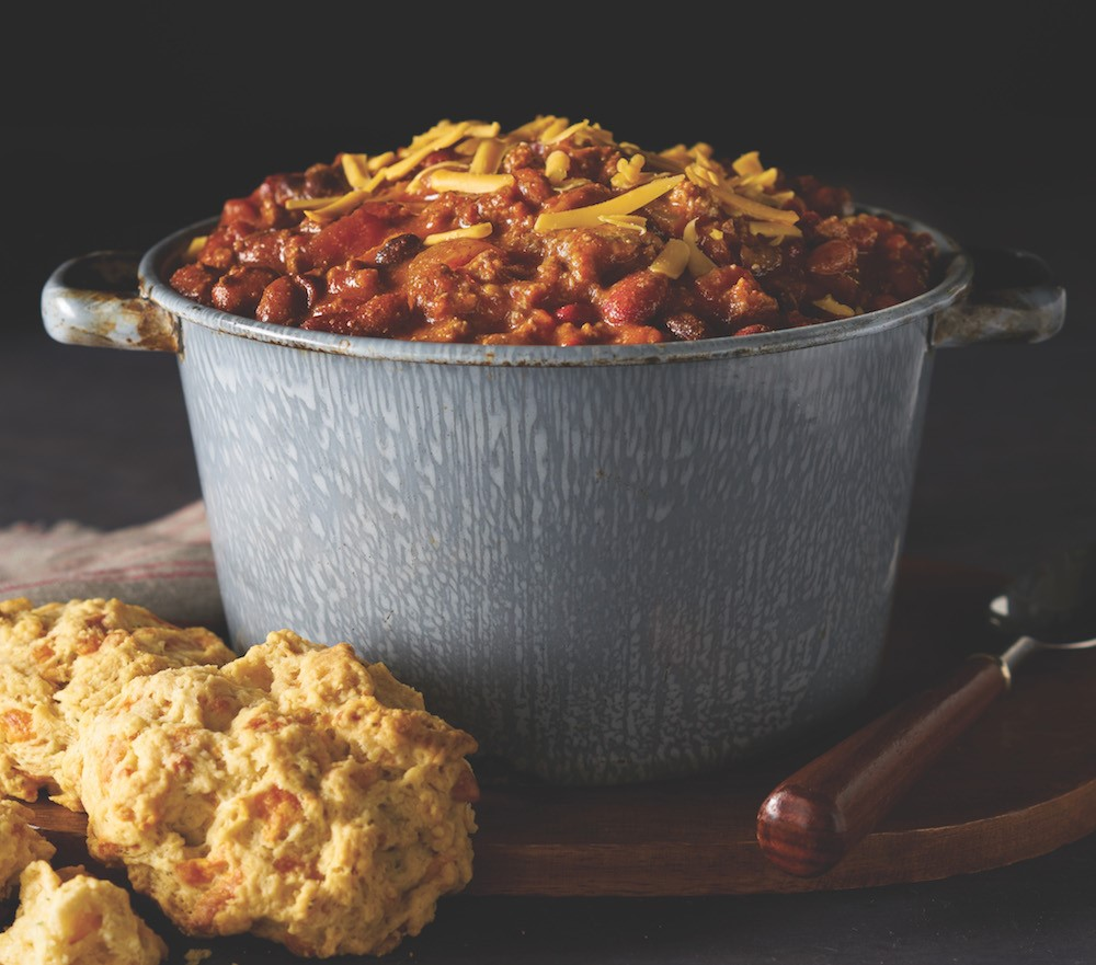 Pot of Chili with Yellow Shredded Cheese and Biscuits on the Side