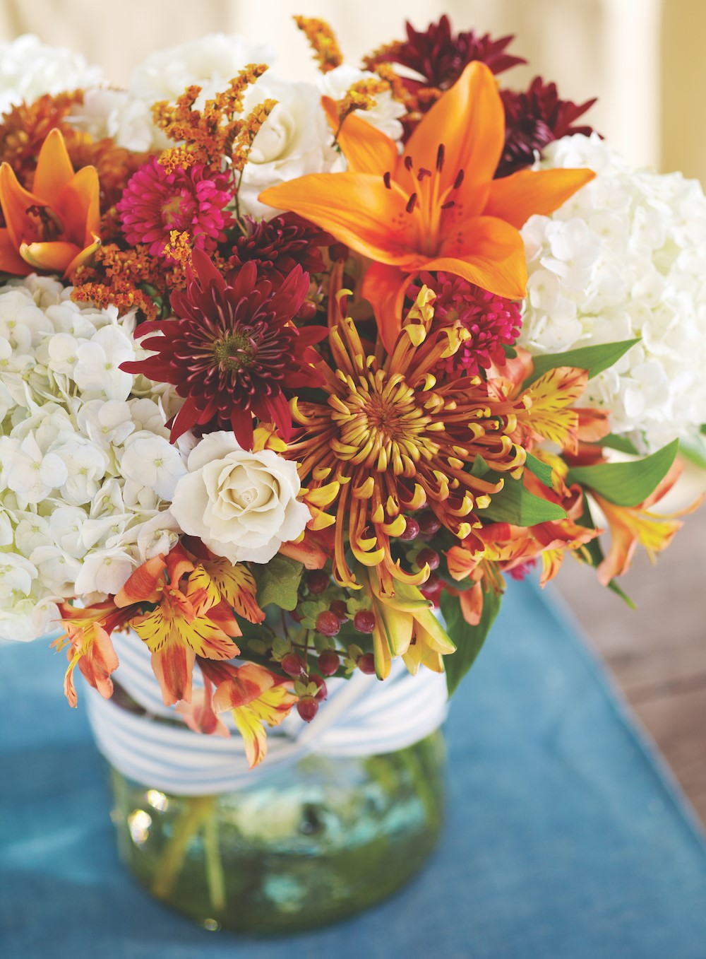 Arrangement of lillies, tiger lillies, hydrangeas, and red and orange mums