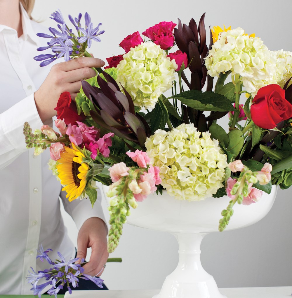 placing flowers in the arrangement