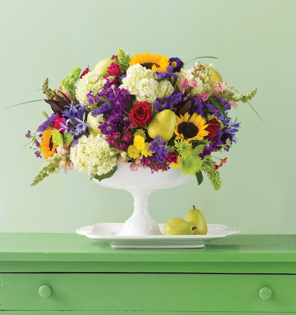pear and wildflower bouquet in a white footed vase