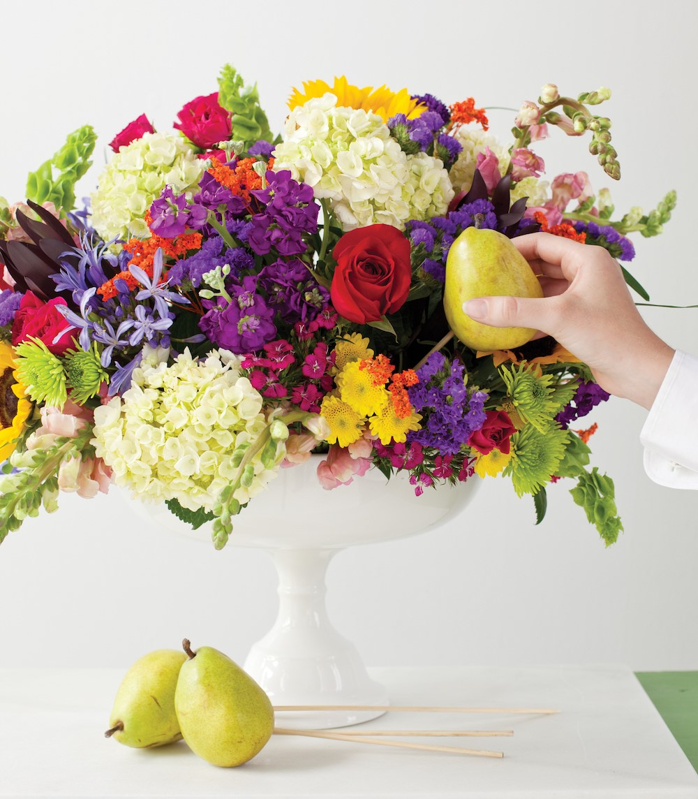 placing a skewered pear into the bouquet