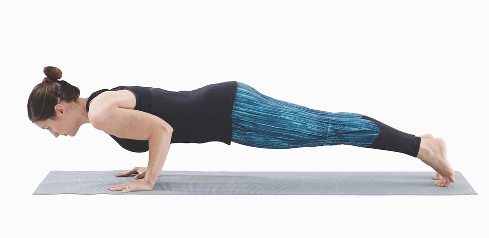 woman in a plank position with elbows bent so that her upper arms are parallel to the floor