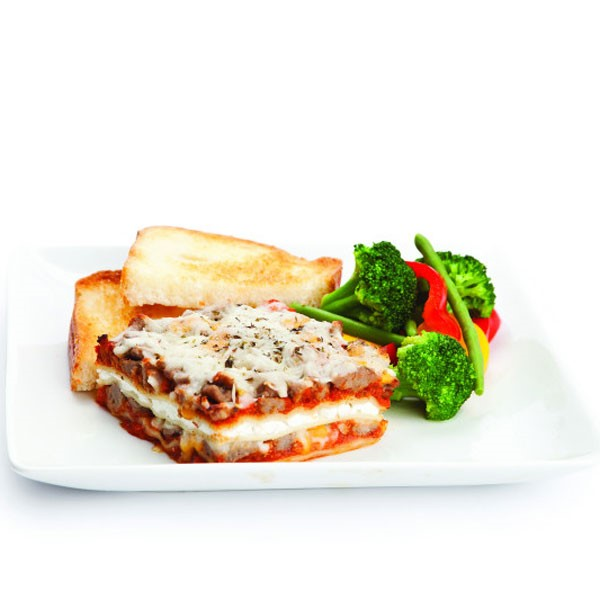 Lasagna on Plate with Veggies and Bread