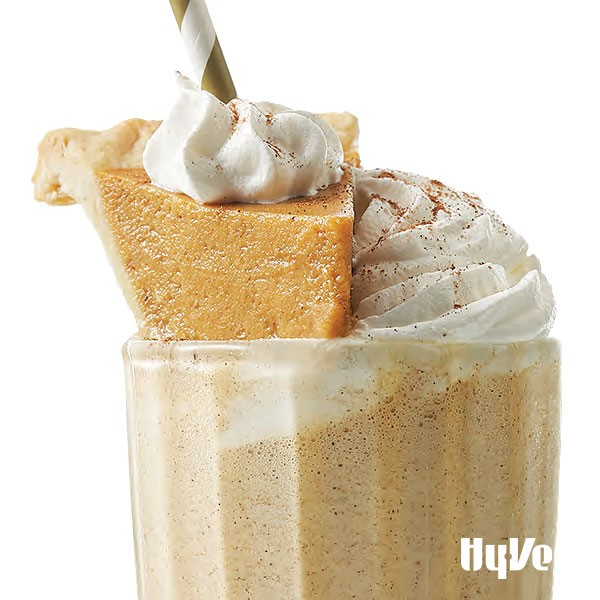 Pumpkin shake with mini pumpkin slice and whipped cream in glass