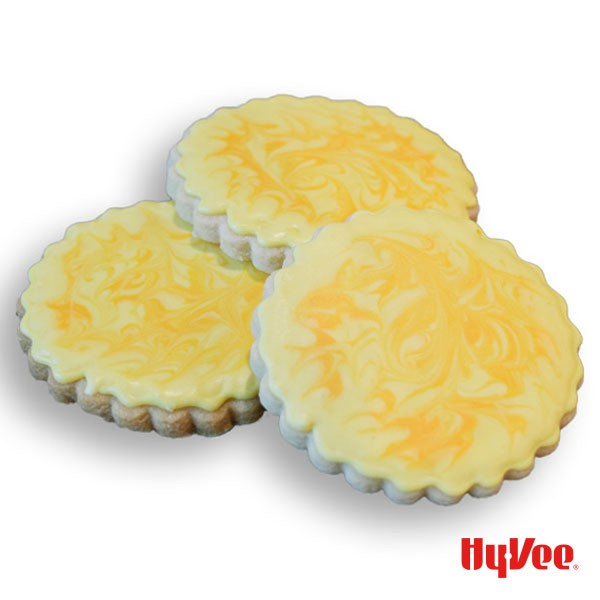 Three cut-out cookies with yellow-marbled royal icing