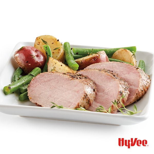 Sliced pork, fresh green beans, halved potatoes, and fresh thyme on a white square plate