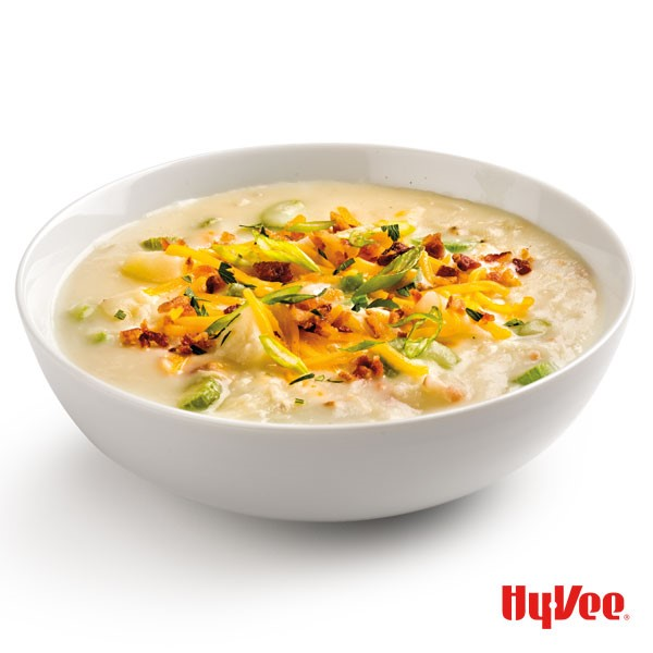 White bowl filled with potato soup and topped with green onions, crumbled bacon, and shredded cheese