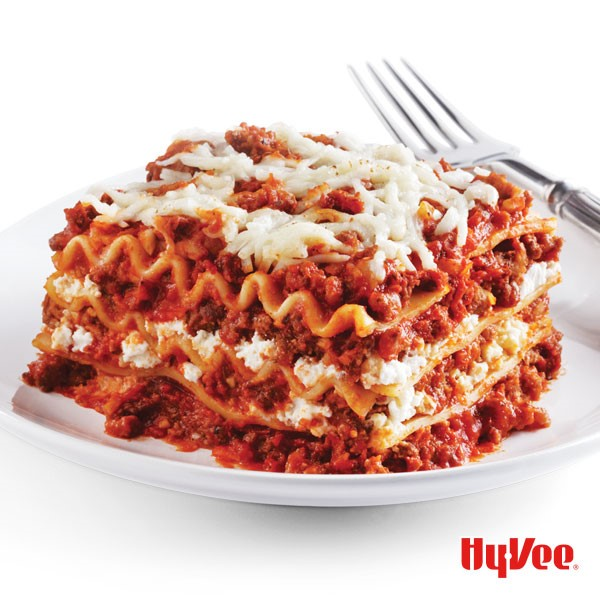 Plate of classic lasagna topped with mozzarella cheese