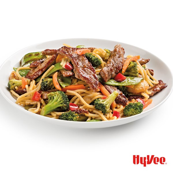 Beef strips, shredded carrots, diced red pepper, broccoli florets, and noodles in a white bowl