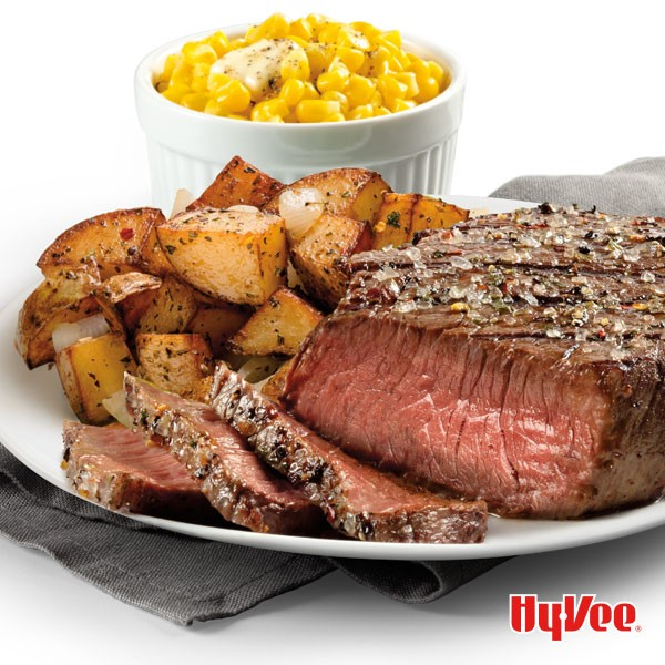 Sliced sirloin steak on a white plate with a side of potatoes and buttered whole-kernel corn