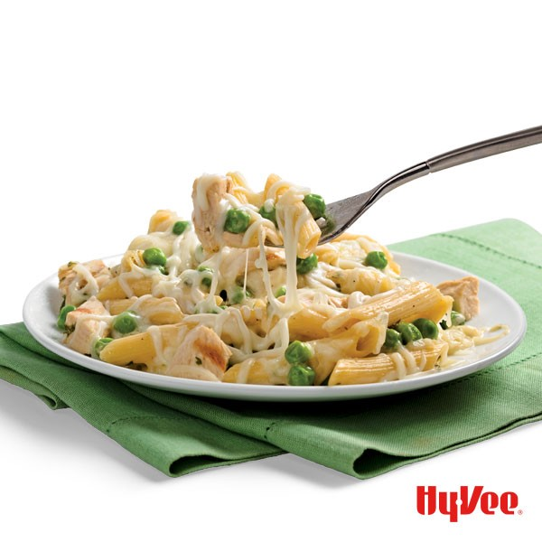 Penne pasta on a plate with a fork digging in