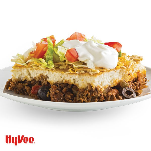 Layered taco bake with ground beef, sliced olives, dough, shredded cheese, shredded lettuce and a dollop of sour cream