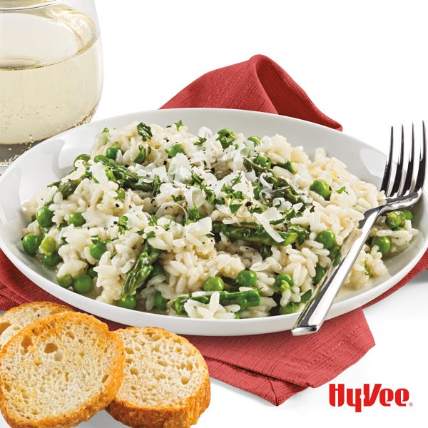 Shallow dish filled with risotto, peas, asparagus, and grated Parmesan cheese with a side of sliced bread, white wine, and fork