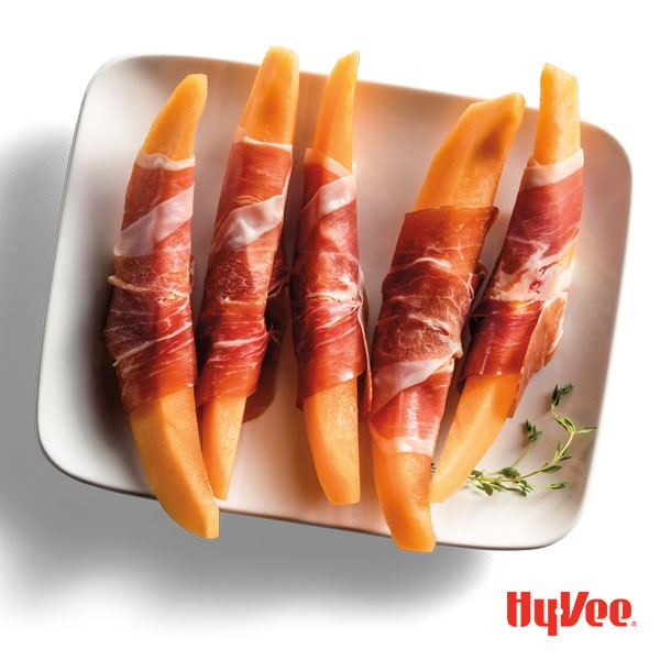 Cantalope wedges wrapped in prosciutto on a white plate with thyme sprigs