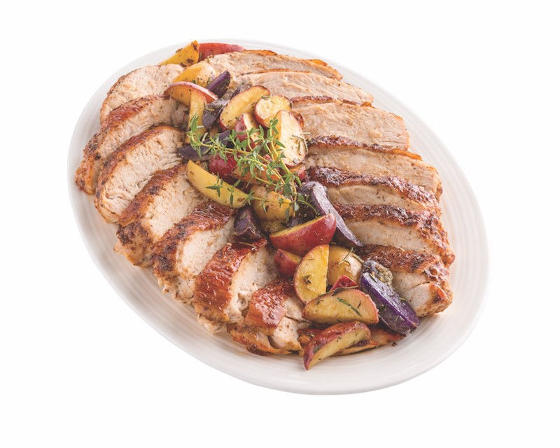 Platter of sliced turkey breast meat with roasted potatoes on top