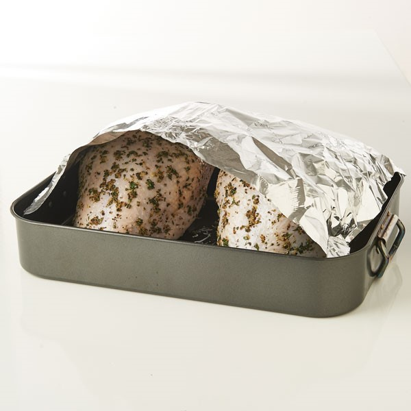Covering raw seasoned turkey breasts in roasting pan with aluminum foil