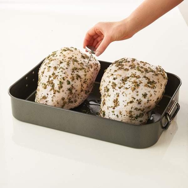 Seasoned turkey breasts in roasting pan inserting thermometer