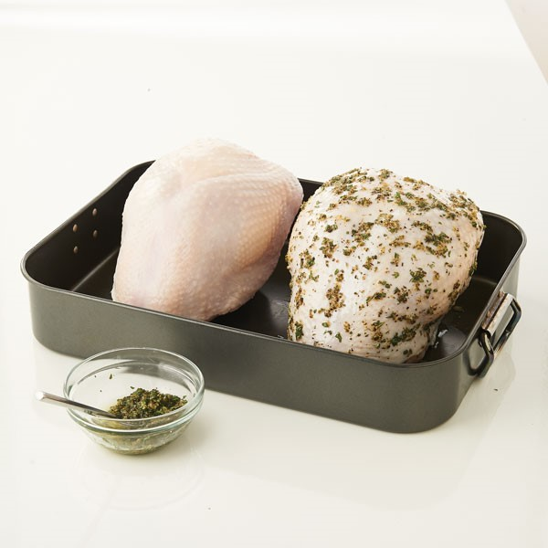 Raw turkey breasts in roasting pan with one covered in spices