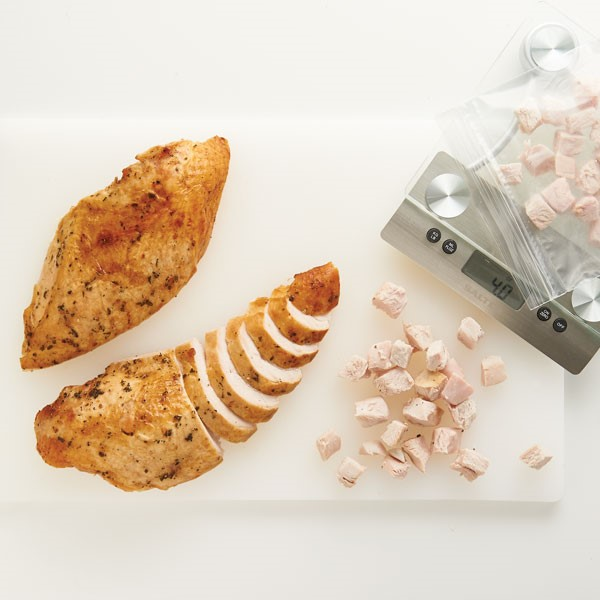 Roasted and spiced turkey breasts sliced and cubed on cutting board with scale