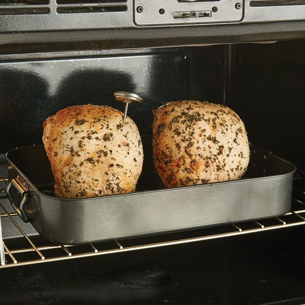 Two turkey breasts in roasting pan in oven with meat thermometer attached