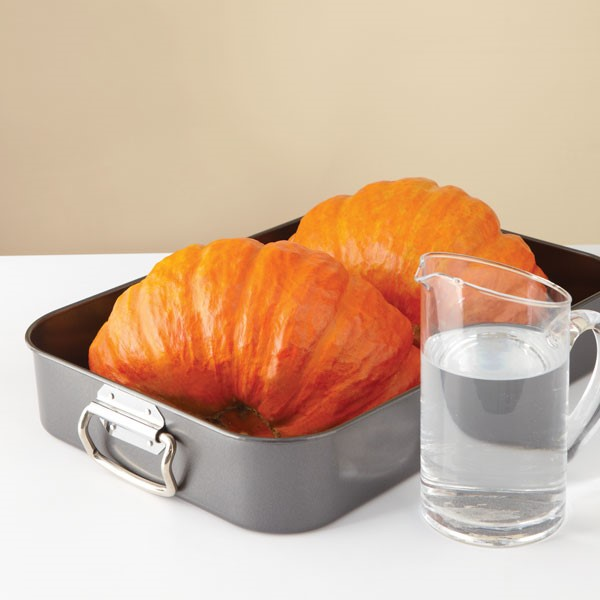 Halved pumpkins in roasting pan next to pitcher of water