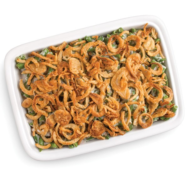 White casserole dish holding white sauced green beans and garnished with crunchy onions