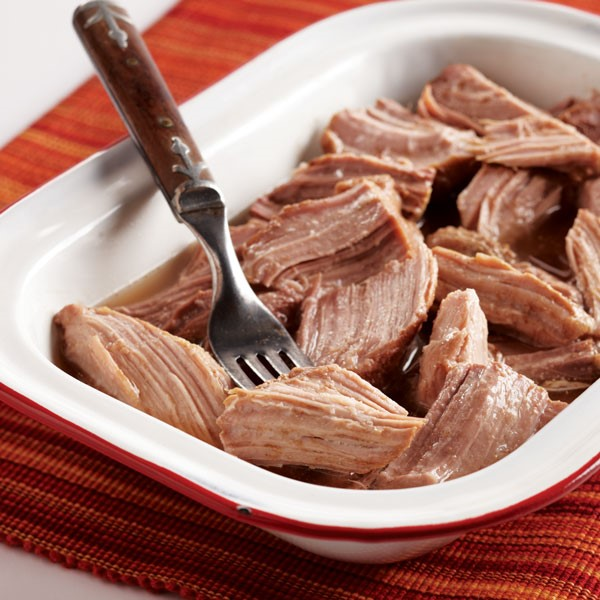 Shaved pork roast in casserole dish with fork