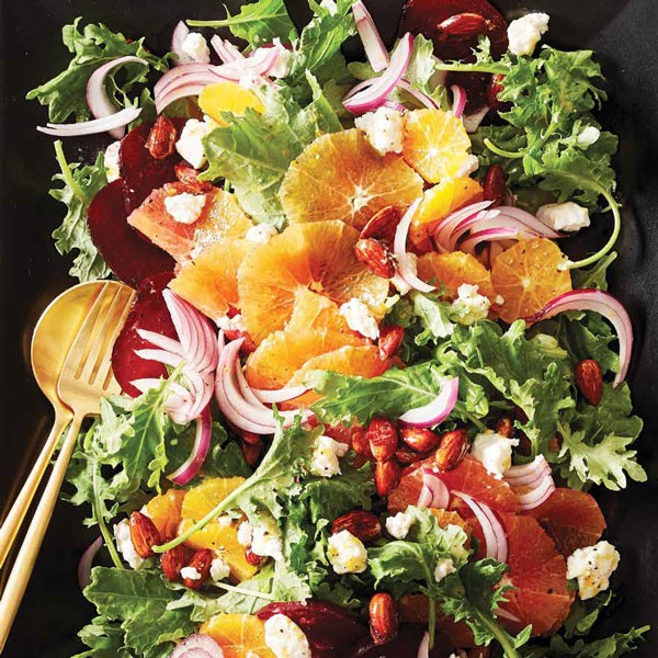 Black platter with gold silverware holding salad with sugared almonds, crumbled goat cheese, sliced red onions, and whole slices of blood oranges