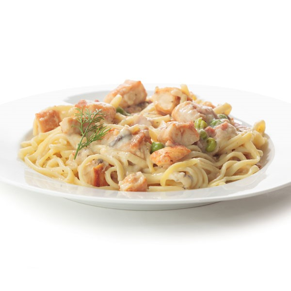 Creamy white sauce pasta holding large pieces of turkey, mushrooms, and peas