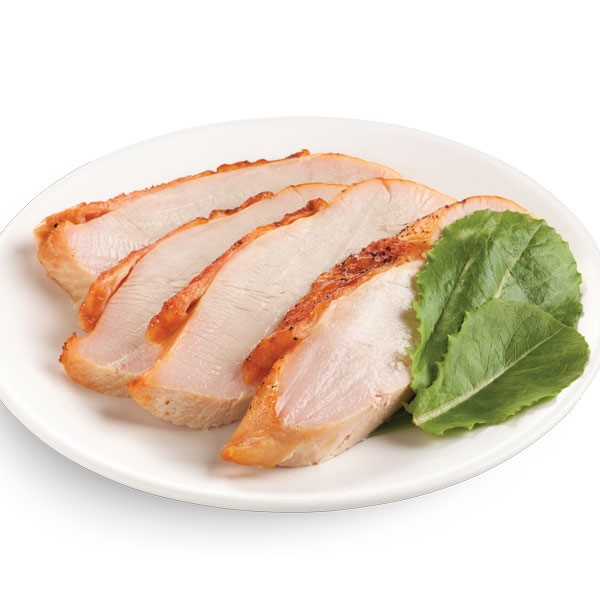 Roasted and sliced turkey breast on a white plate with spinach leaves for garnish