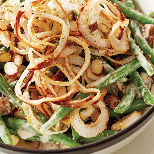Green beans with creamy white sauce topped with homemade crispy onions and sliced almonds